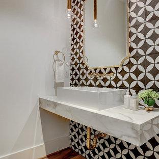 Réalisation d'un WC et toilettes design avec un carrelage noir et blanc, des carreaux de béton, un mur blanc, un sol en bois brun, une vasque et un sol marron.