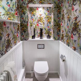 Cette image montre un WC et toilettes traditionnel avec un WC suspendu, un mur multicolore et un sol gris.