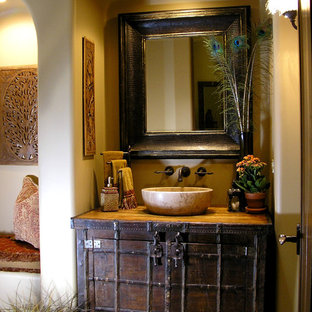 Powder room - traditional powder room idea in Phoenix with a vessel sink, wood countertops, brown countertops, furniture-like cabinets, dark wood cabinets and beige walls