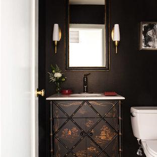 На фото: туалеты в классическом стиле с фасадами островного типа, черными стенами и белой столешницей