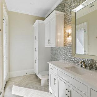 Cette image montre un WC et toilettes traditionnel de taille moyenne avec un placard avec porte à panneau encastré, des portes de placard blanches, un WC à poser, un carrelage multicolore, carrelage en mosaïque, un mur beige, un sol en carrelage de céramique, un lavabo encastré, un plan de toilette en quartz modifié, un sol beige, un plan de toilette blanc et meuble-lavabo encastré.