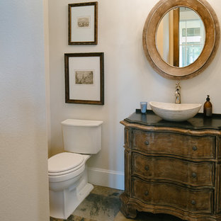 Small rustic cloakroom in Houston with a vessel sink, medium wood cabinets, granite worktops, a two-piece toilet, beige walls and slate flooring.