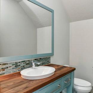 Idées déco pour un WC et toilettes campagne de taille moyenne avec un placard à porte plane, un mur gris, des portes de placard turquoises, un carrelage bleu, carrelage en mosaïque, un sol en bois peint, un lavabo posé, un plan de toilette en bois, un sol multicolore et un plan de toilette marron.