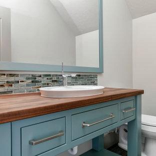 Пример оригинального дизайна: туалет среднего размера в стиле кантри с плоскими фасадами, бирюзовыми фасадами, синей плиткой, плиткой мозаикой, серыми стенами, деревянным полом, накладной раковиной, столешницей из дерева, разноцветным полом и коричневой столешницей