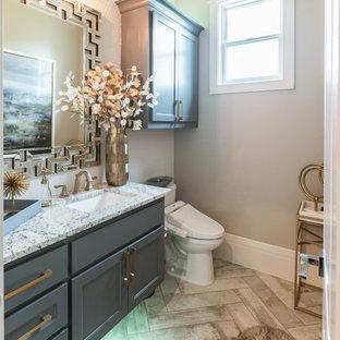 Cette image montre un grand WC et toilettes traditionnel avec un placard avec porte à panneau surélevé, des portes de placard grises, un bidet, un carrelage blanc, carrelage en mosaïque, un mur beige, un sol en carrelage de céramique, un lavabo encastré, un plan de toilette en granite, un sol beige et un plan de toilette gris.