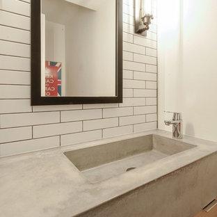 Пример оригинального дизайна: маленький туалет в стиле современная классика с плоскими фасадами, светлыми деревянными фасадами, унитазом-моноблоком, белой плиткой, плиткой кабанчик, белыми стенами, полом из сланца, монолитной раковиной, столешницей из бетона и серым полом