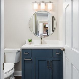 Klassisk inredning av ett litet vit vitt toalett, med luckor med infälld panel, blå skåp, en toalettstol med separat cisternkåpa, mellanmörkt trägolv, ett undermonterad handfat, bänkskiva i kvartsit, brunt golv och beige väggar