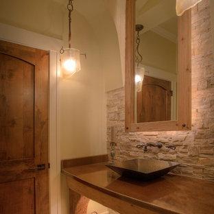 デトロイトの大きいラスティックスタイルのおしゃれなトイレ・洗面所 (フラットパネル扉のキャビネット、中間色木目調キャビネット、ベージュのタイル、石タイル、ベージュの壁、セラミックタイルの床、ベッセル式洗面器、銅の洗面台、ブラウンの洗面カウンター) の写真
