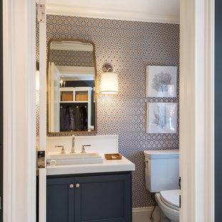 Cette image montre un petit WC et toilettes traditionnel avec des portes de placard bleues, un WC séparé, un carrelage blanc, un mur multicolore, un lavabo posé, un plan de toilette en surface solide, un placard à porte affleurante et un plan de toilette blanc.