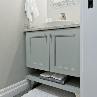 Foto di un bagno di servizio tradizionale con lavabo a bacinella, ante con riquadro incassato, ante grigie, top in granito e pavimento in gres porcellanato