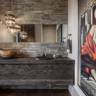 他の地域のラスティックスタイルのおしゃれなトイレ・洗面所 (濃色木目調キャビネット、グレーのタイル、白い壁、濃色無垢フローリング、木製洗面台、茶色い床、オーバーカウンターシンク、グレーの洗面カウンター) の写真