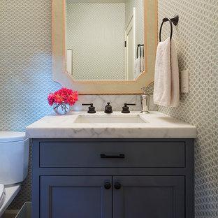 Immagine di un piccolo bagno di servizio tradizionale con ante grigie, lavabo sottopiano, top in marmo, WC a due pezzi e ante con riquadro incassato