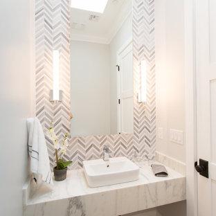 Стильный дизайн: большой туалет в современном стиле с серой плиткой, настольной раковиной, мраморной столешницей, серыми стенами, паркетным полом среднего тона, серым полом, мраморной плиткой и открытыми фасадами - последний тренд