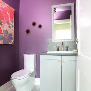 Cette photo montre un petit WC et toilettes chic avec un placard à porte shaker, un WC séparé, un carrelage gris, carrelage en mosaïque, un mur violet, un sol en carrelage de céramique, une vasque, un plan de toilette en quartz modifié et des portes de placard beiges.