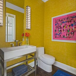 Cette image montre un WC et toilettes traditionnel de taille moyenne avec un placard sans porte, un WC à poser, un mur jaune, un sol en bois foncé, un plan vasque et un sol marron.