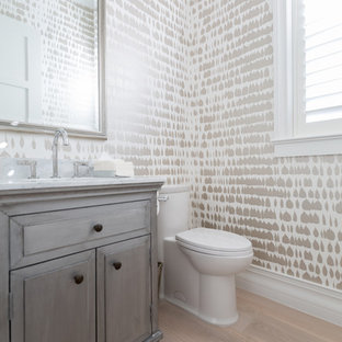 This is an example of a medium sized classic cloakroom in Miami with raised-panel cabinets, grey cabinets, a two-piece toilet, light hardwood flooring, a submerged sink, marble worktops and beige floors.