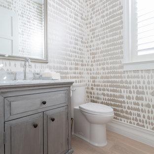 Foto di un bagno di servizio chic di medie dimensioni con ante con bugna sagomata, ante grigie, WC a due pezzi, parquet chiaro, lavabo sottopiano, top in marmo e pavimento beige