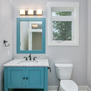 На фото: туалет в стиле современная классика с фасадами в стиле шейкер, бирюзовыми фасадами, раздельным унитазом, серыми стенами, врезной раковиной, серым полом и серой столешницей