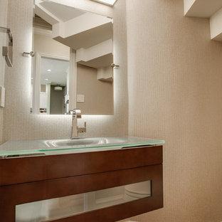 Kleine Moderne Gästetoilette mit integriertem Waschbecken, Glasfronten, dunklen Holzschränken, Glaswaschbecken/Glaswaschtisch, Wandtoilette, beiger Wandfarbe und braunem Holzboden in Dallas