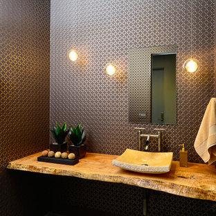На фото: туалеты среднего размера в современном стиле с настольной раковиной, столешницей из дерева, разноцветными стенами, бетонным полом и коричневой столешницей
