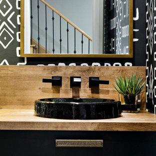 Cette image montre un WC et toilettes bohème de taille moyenne avec un placard à porte plane, des portes de placard noires, un WC à poser, un mur noir, un sol en carrelage de porcelaine, une vasque, un plan de toilette en bois, un sol blanc, un plan de toilette marron, meuble-lavabo encastré et du papier peint.