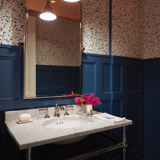 Example of a mid-sized classic powder room design in New York with multicolored walls and a console sink