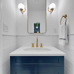 ニューヨークのトランジショナルスタイルのおしゃれなトイレ・洗面所 (シェーカースタイル扉のキャビネット、青いキャビネット、白いタイル、白い壁、アンダーカウンター洗面器、白い洗面カウンター) の写真
