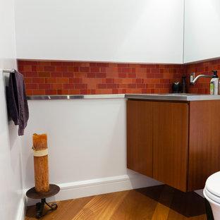 Idée de décoration pour un WC et toilettes design avec un placard à porte plane, des portes de placard en bois sombre, un WC suspendu, un carrelage rouge, des carreaux de céramique, un mur blanc, un sol en bois brun, un lavabo intégré et un plan de toilette en acier inoxydable.