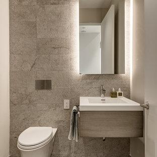 Modelo de aseo actual con sanitario de pared, armarios con paneles lisos, puertas de armario grises, baldosas y/o azulejos grises, paredes blancas, lavabo tipo consola y suelo marrón