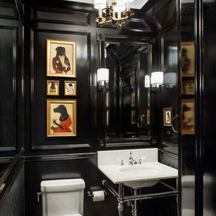 Elegant powder room photo in New York with an undermount sink and black walls