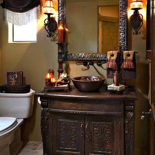 На фото: туалет среднего размера в средиземноморском стиле с настольной раковиной, фасадами островного типа, темными деревянными фасадами, столешницей из дерева, унитазом-моноблоком, бежевой плиткой, бежевыми стенами, полом из травертина, бежевым полом и коричневой столешницей с