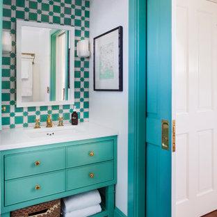 Cette image montre un WC et toilettes ethnique avec des portes de placards vertess, un carrelage bleu, un carrelage vert, un mur blanc, un lavabo encastré, un sol vert, un placard à porte affleurante et un plan de toilette blanc.