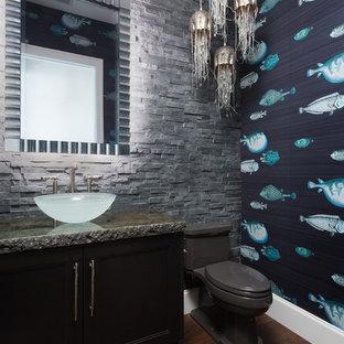 マイアミの中くらいのトロピカルスタイルのおしゃれなトイレ・洗面所 (落し込みパネル扉のキャビネット、濃色木目調キャビネット、グレーのタイル、石タイル、ベッセル式洗面器、御影石の洗面台、分離型トイレ、マルチカラーの壁、濃色無垢フローリング、茶色い床) の写真