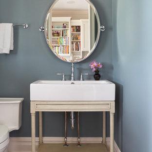 Idée de décoration pour un petit WC et toilettes tradition avec un placard sans porte, des portes de placard beiges, un WC à poser, une vasque, un sol marron, un mur bleu et un sol en carrelage de céramique.