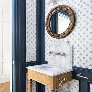 На фото: туалет в классическом стиле с светлыми деревянными фасадами, синими стенами, светлым паркетным полом, консольной раковиной, коричневым полом и белой столешницей с