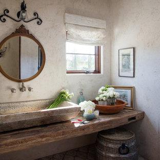 Стильный дизайн: туалет в средиземноморском стиле с бежевыми стенами, настольной раковиной, столешницей из дерева и коричневой столешницей - последний тренд