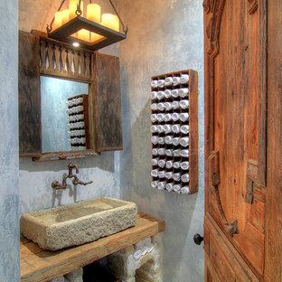 Inredning av ett medelhavsstil toalett, med ett fristående handfat, träbänkskiva och grå väggar