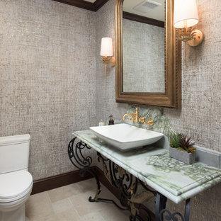 ロサンゼルスのおしゃれなトイレ・洗面所 (一体型トイレ、茶色い壁、ライムストーンの床、コンソール型シンク、ベージュの床、グリーンの洗面カウンター) の写真
