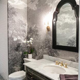 На фото: туалеты в классическом стиле с фасадами островного типа, искусственно-состаренными фасадами, раздельным унитазом, разноцветными стенами, врезной раковиной, серым полом и белой столешницей