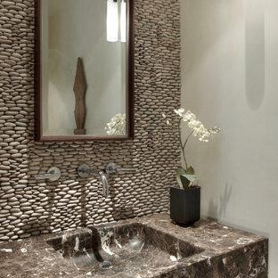 Idées déco pour un WC et toilettes contemporain avec un placard à porte plane, des portes de placard en bois brun, un carrelage beige, carrelage en mosaïque, un mur beige, un lavabo intégré, un plan de toilette en marbre, un plan de toilette marron et meuble-lavabo encastré.