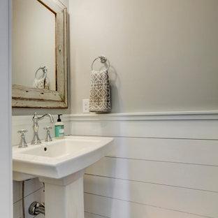 Стильный дизайн: туалет в стиле кантри с серыми стенами, паркетным полом среднего тона, раковиной с пьедесталом и коричневым полом - последний тренд