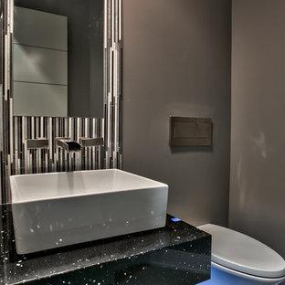 Foto di un piccolo bagno di servizio minimalista con nessun'anta, ante grigie, WC sospeso, pistrelle in bianco e nero, piastrelle di vetro, pareti grigie, pavimento in gres porcellanato, lavabo a bacinella e top in superficie solida