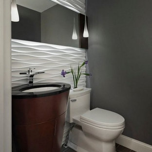 This is an example of a small contemporary cloakroom in San Francisco with grey walls, a one-piece toilet, dark wood cabinets, white tiles, ceramic tiles, porcelain flooring, a submerged sink, granite worktops, grey floors and black worktops.