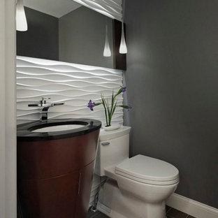 Idées déco pour un petit WC et toilettes contemporain avec un mur gris, un WC à poser, des portes de placard en bois sombre, un carrelage blanc, des carreaux de céramique, un sol en carrelage de porcelaine, un lavabo encastré, un plan de toilette en granite, un sol gris et un plan de toilette noir.