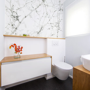 This is an example of a medium sized modern cloakroom in Frankfurt with flat-panel cabinets, white cabinets, a wall mounted toilet, white walls, a vessel sink and wooden worktops.