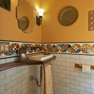 Mediterranean cloakroom in Portland with a vessel sink, wooden worktops and multi-coloured tiles.