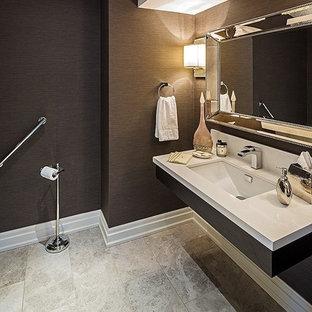 Cette image montre un grand WC et toilettes traditionnel avec un lavabo encastré, un mur noir et un carrelage beige.
