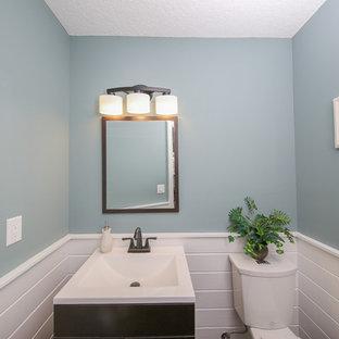タンパの小さいトランジショナルスタイルのおしゃれなトイレ・洗面所 (濃色木目調キャビネット、白いタイル、青い壁、一体型シンク、分離型トイレ) の写真