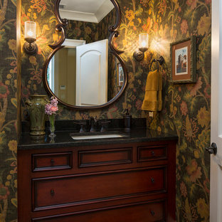 Elegant powder room photo in Minneapolis with an undermount sink, recessed-panel cabinets, dark wood cabinets and black countertops