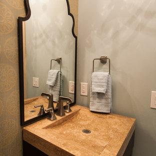 Inspiration för klassiska toaletter, med ett integrerad handfat, en toalettstol med separat cisternkåpa, möbel-liknande, skåp i mörkt trä, bänkskiva i travertin och beige kakel